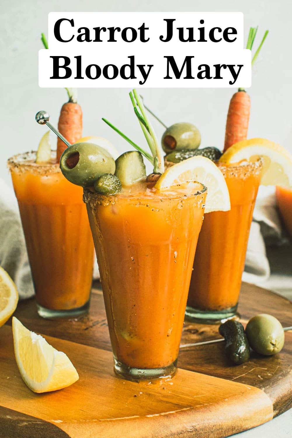 Carrot juice Bloody Mary in glasses topped with garnishes on a wooden board.