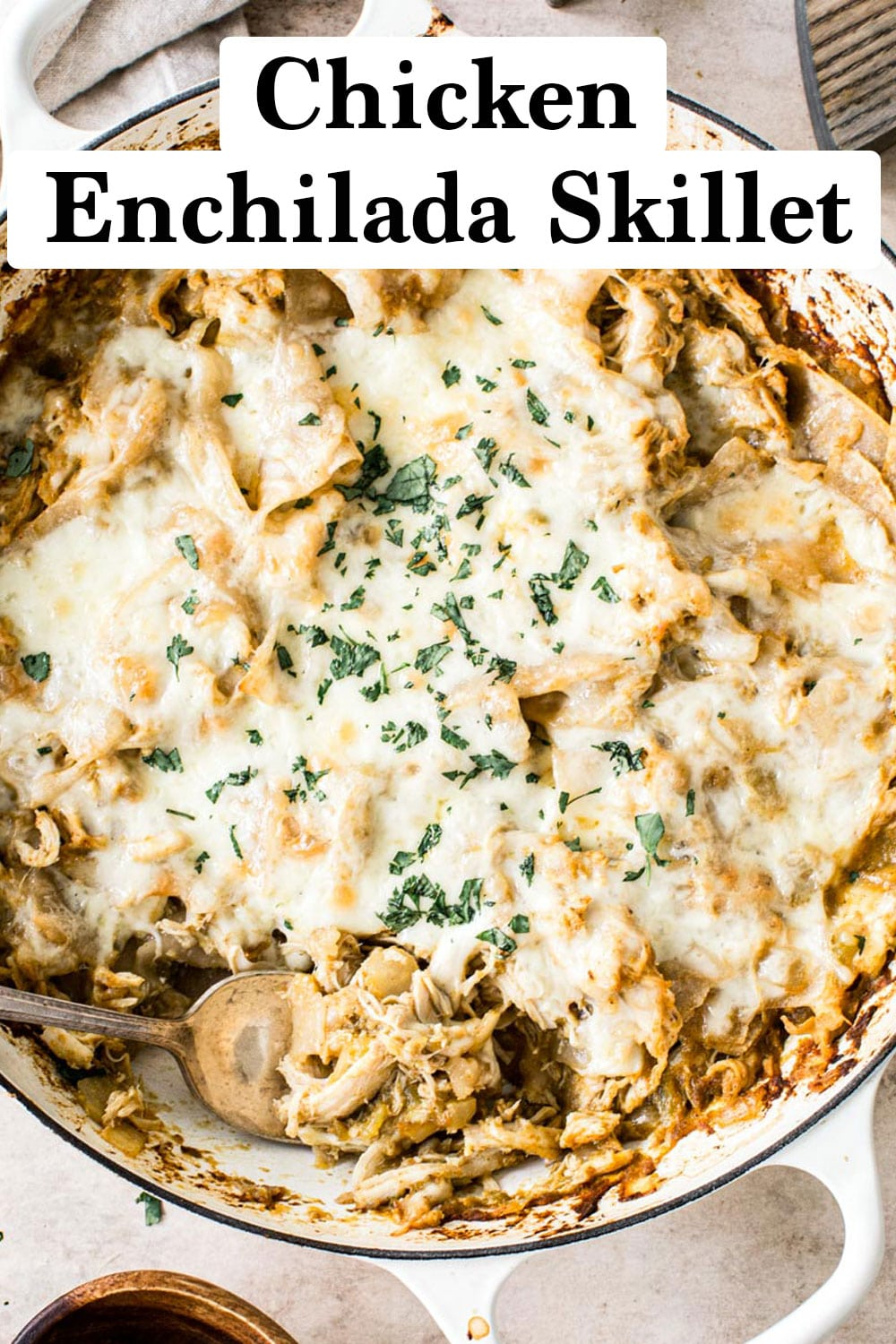 Chicken enchilada skillet topped with cheese and fresh cilantro in a white skillet.