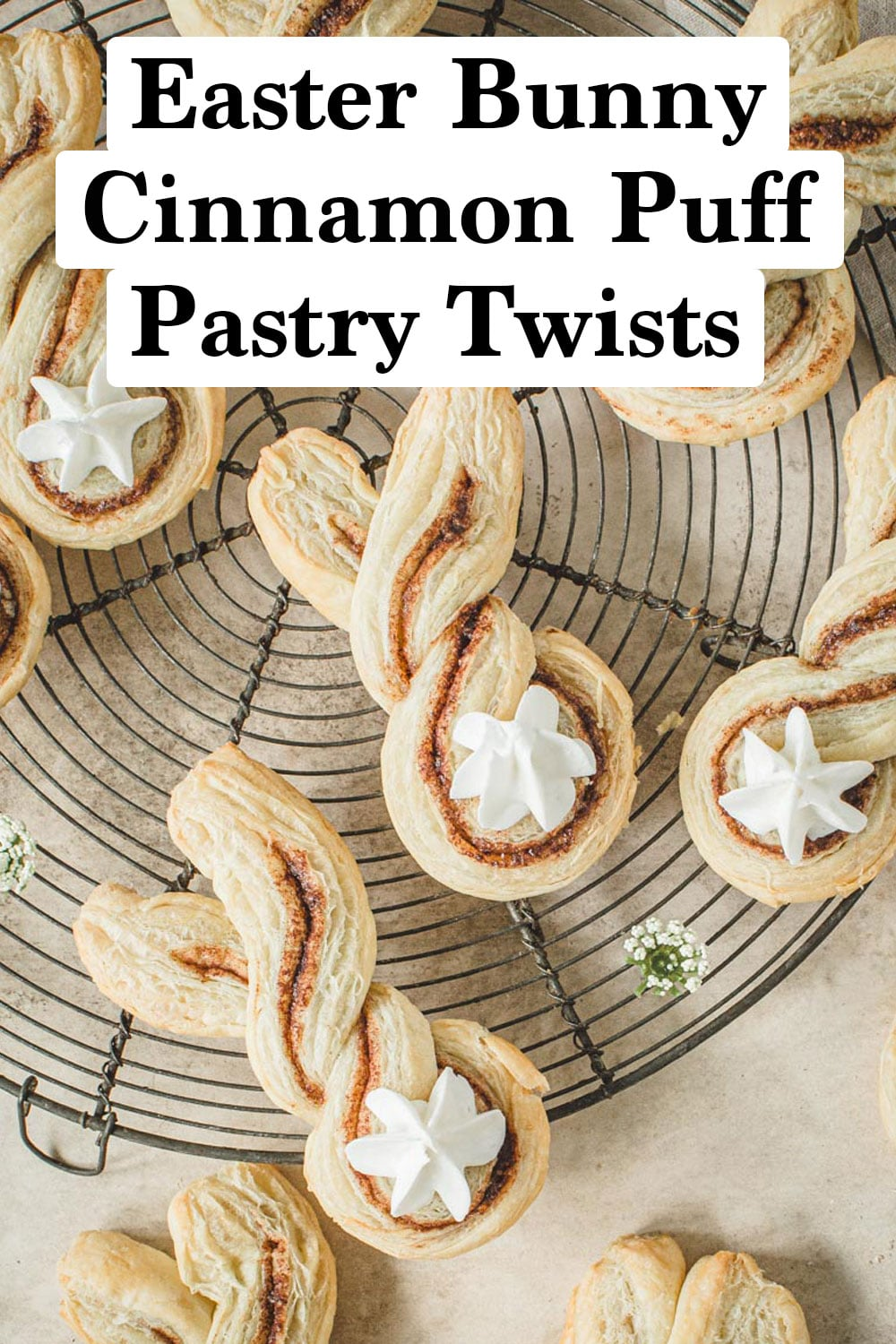 Cinnamon puff pastries shaped like bunnies with frosting tails on a wire rack.