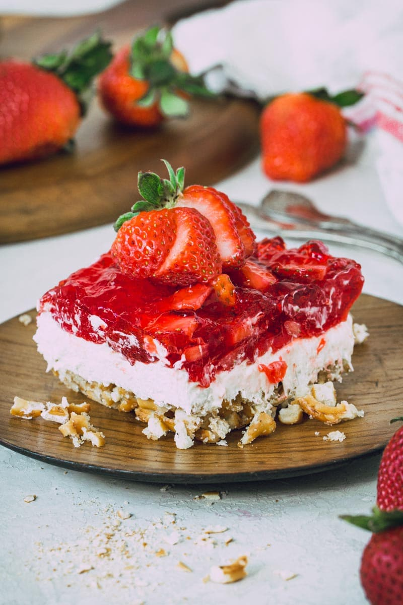 Gluten-free strawberry pretzel salad topped with a sliced strawberry.
