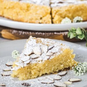 Slice of lemon ricotta almond cake on a white plate with almonds surrounding it and powdered sugar dusted on top.
