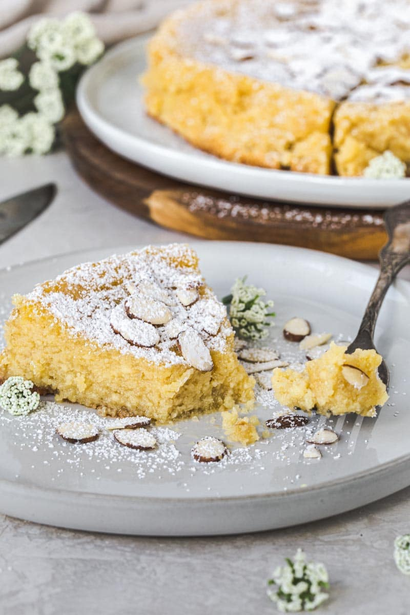 Slice of lemon ricotta almond cake with fork holding a bite sitting on a white plate.