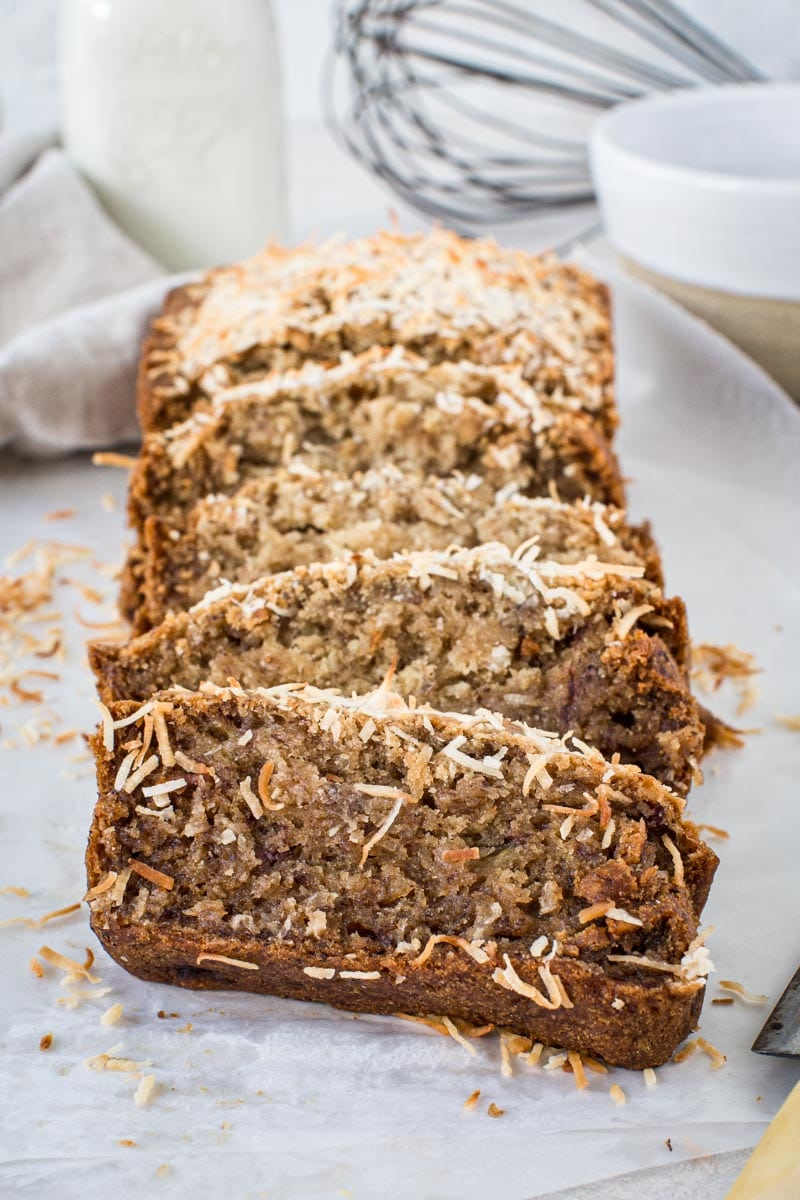 Slices of vegan banana bread topped with toasted coconut on wax paper.