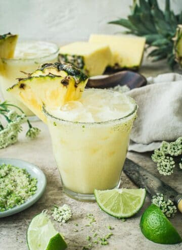 Pineapple coconut margarita with a sugared rim and pineapple wedge on the glass.