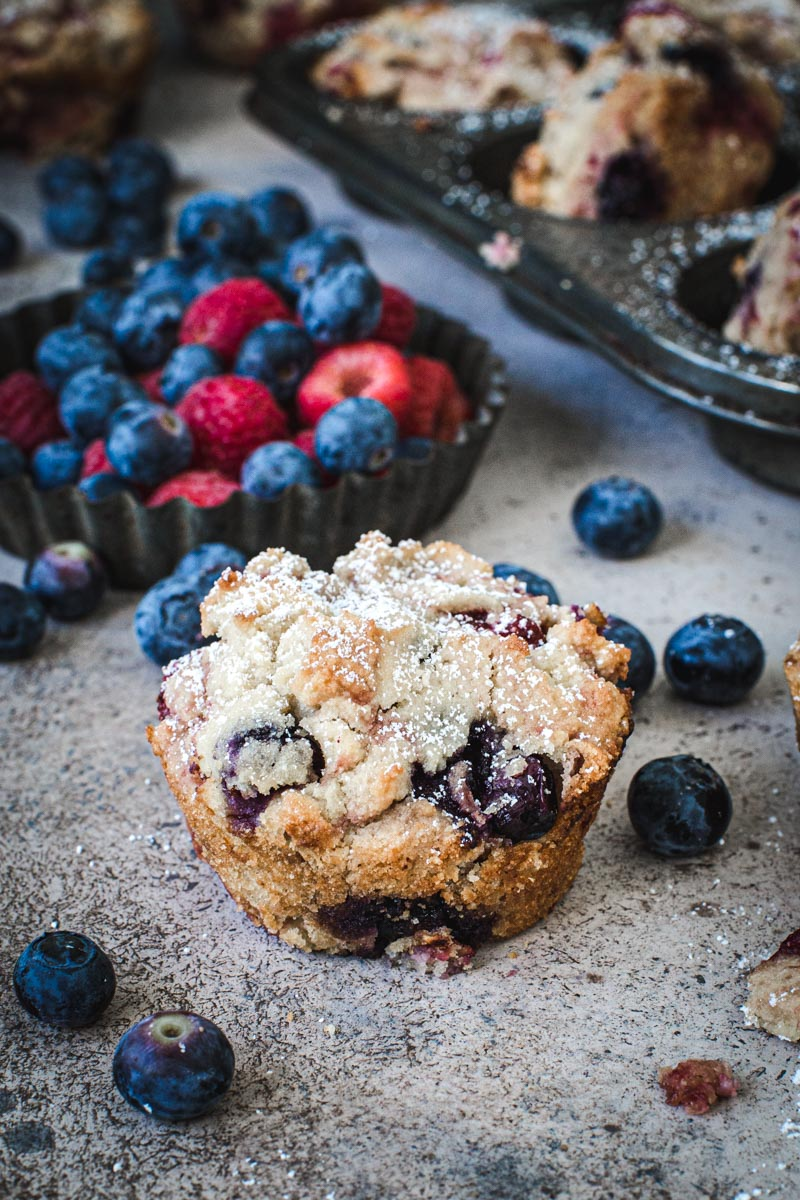 Powdered sugar coated mixed berry cornbread muffin with blueberries and raspberries surrounding it.