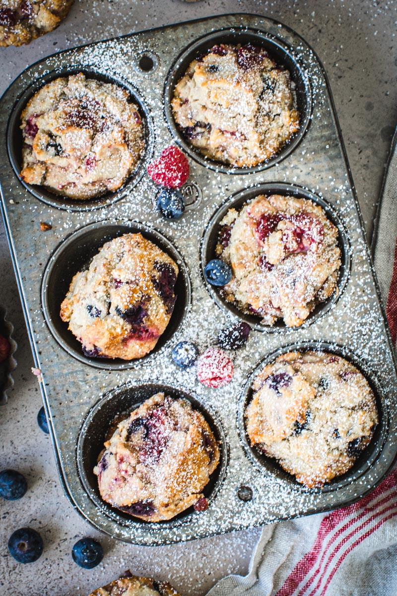 Muffin tin filled with mixed berry cornbread muffins.