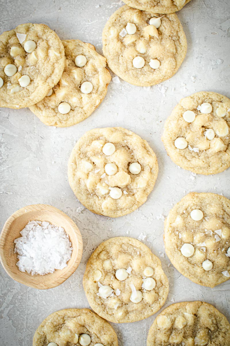 Salted white chocolate chip cookies spread out on a surface with a small bowl of salt flakes next to them.