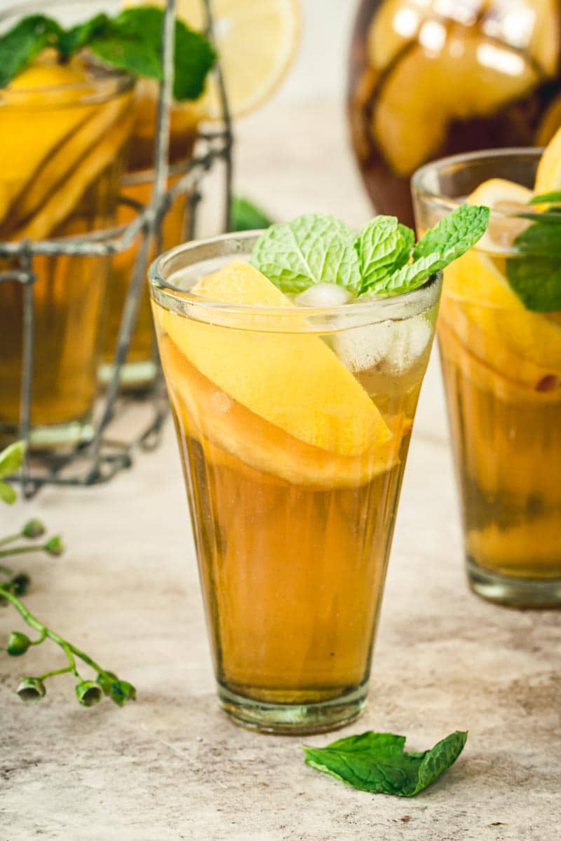Tall glass of sangria iced tea filled with peaches and lemon and topped with mint.