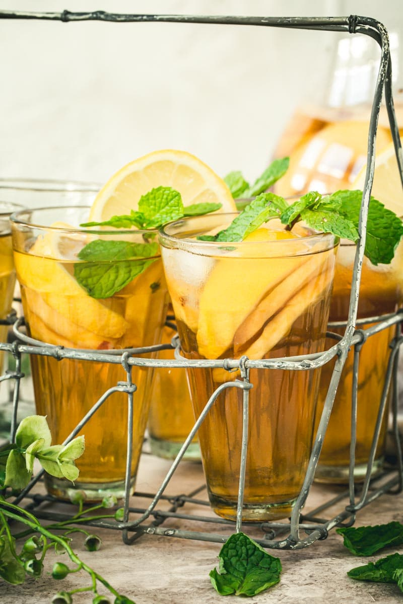 Mint topped sangria iced tea in glasses sitting in a metal drink carrier.