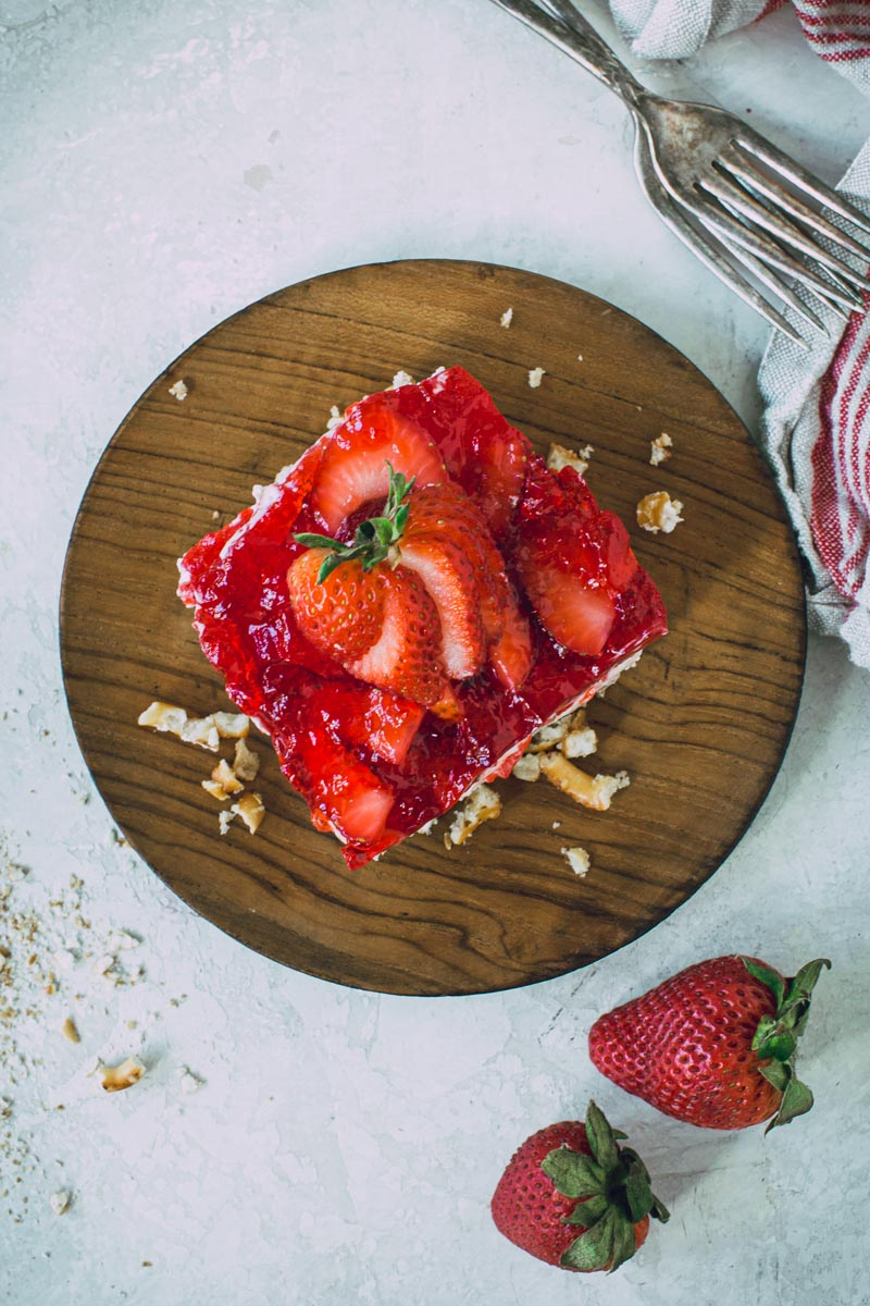 Sliced strawberry on top of strawberry pretzel salad on a wooden plate.