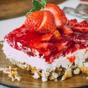 Gluten-free strawberry pretzel salad on a wooden plate.