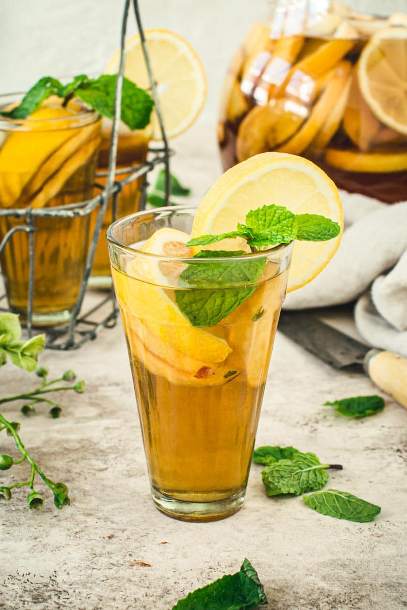 Lemon and mint topped over sangria iced tea in a glass.