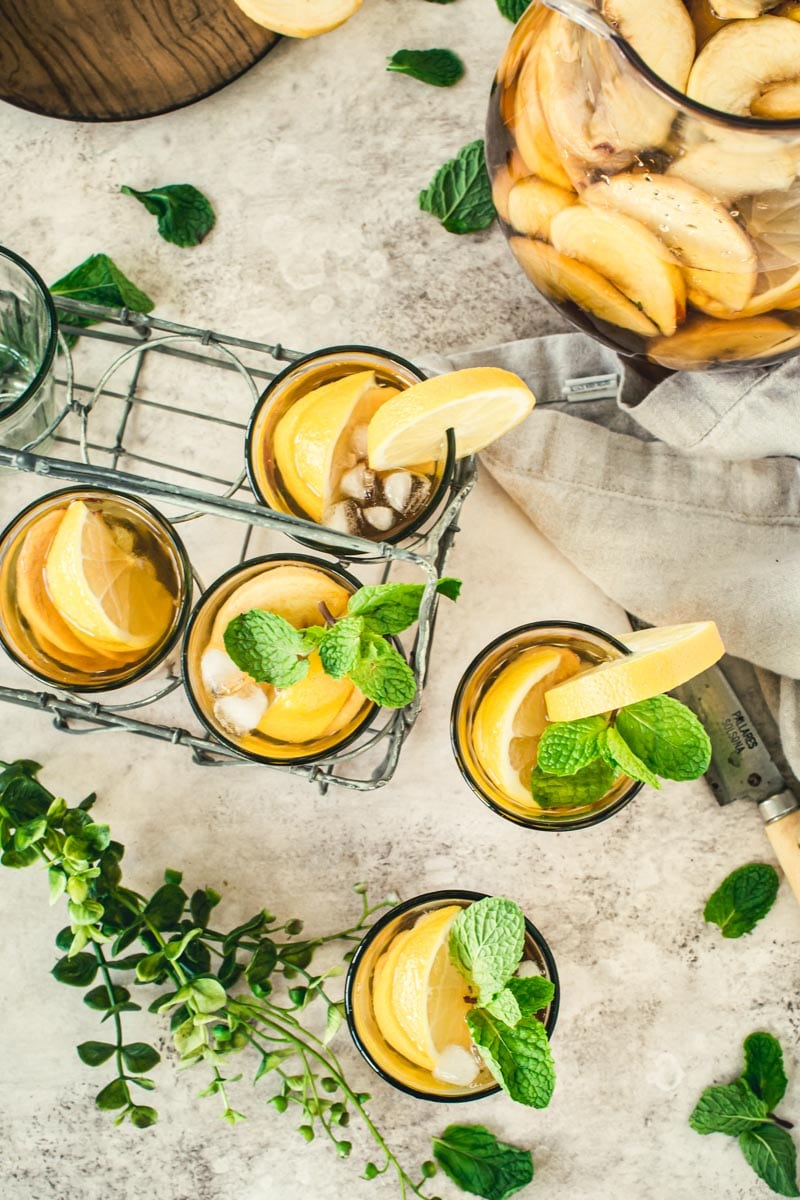Table scattered with glasses filled with sangria iced tea and a pitcher with greenery and mint leaves surrounding.