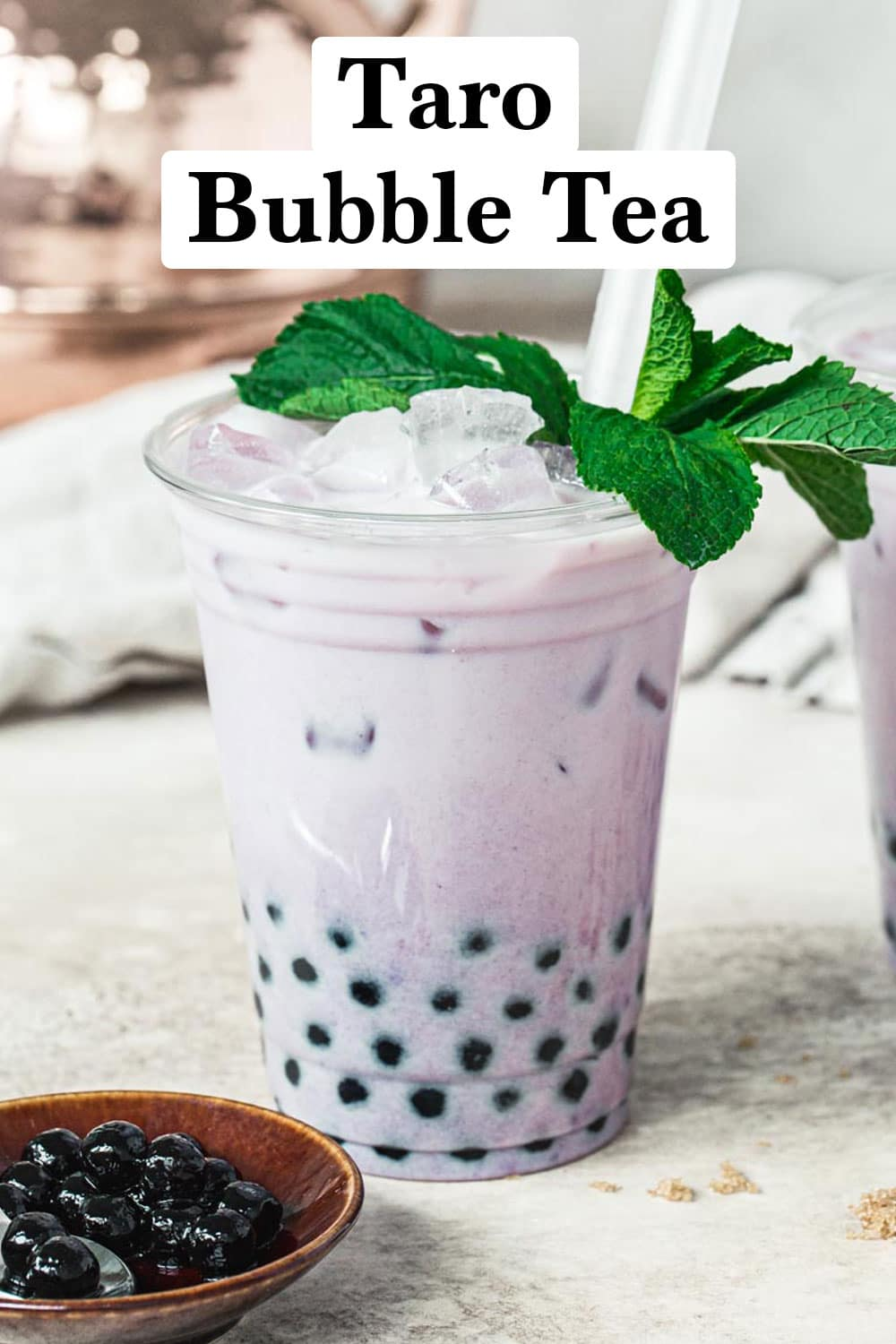 Taro bubble tea in a plastic cup topped with mint leaves and with black and white title.