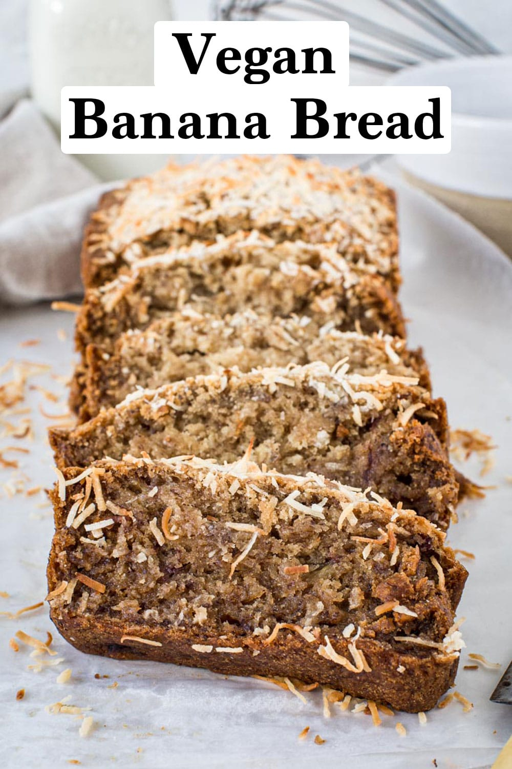Sliced vegan banana bread topped with coconut flakes.