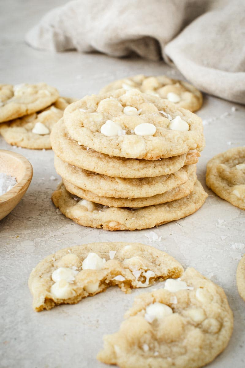 Salted white chocolate chip cookies stacked on top of each other.