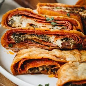 Stromboli slices stacked on a white plate.