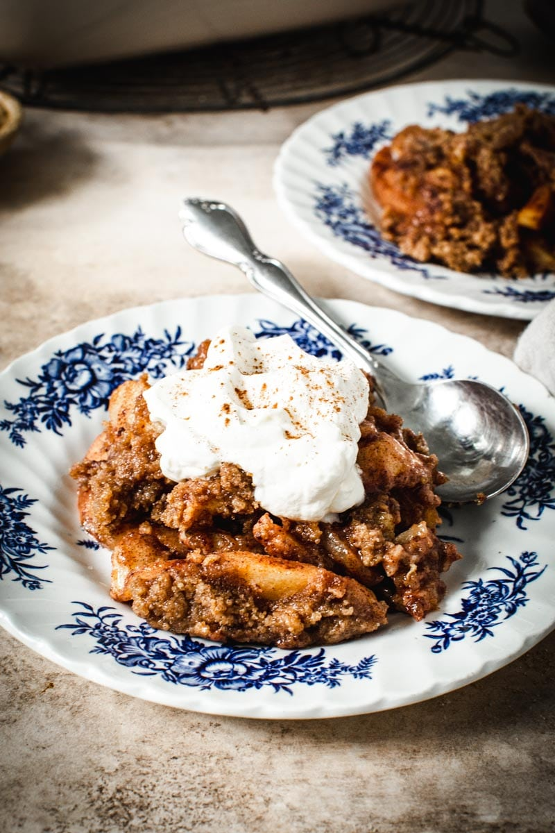 Apple banana crumble topped with whipped cream on a blue and white plate with a spoon.
