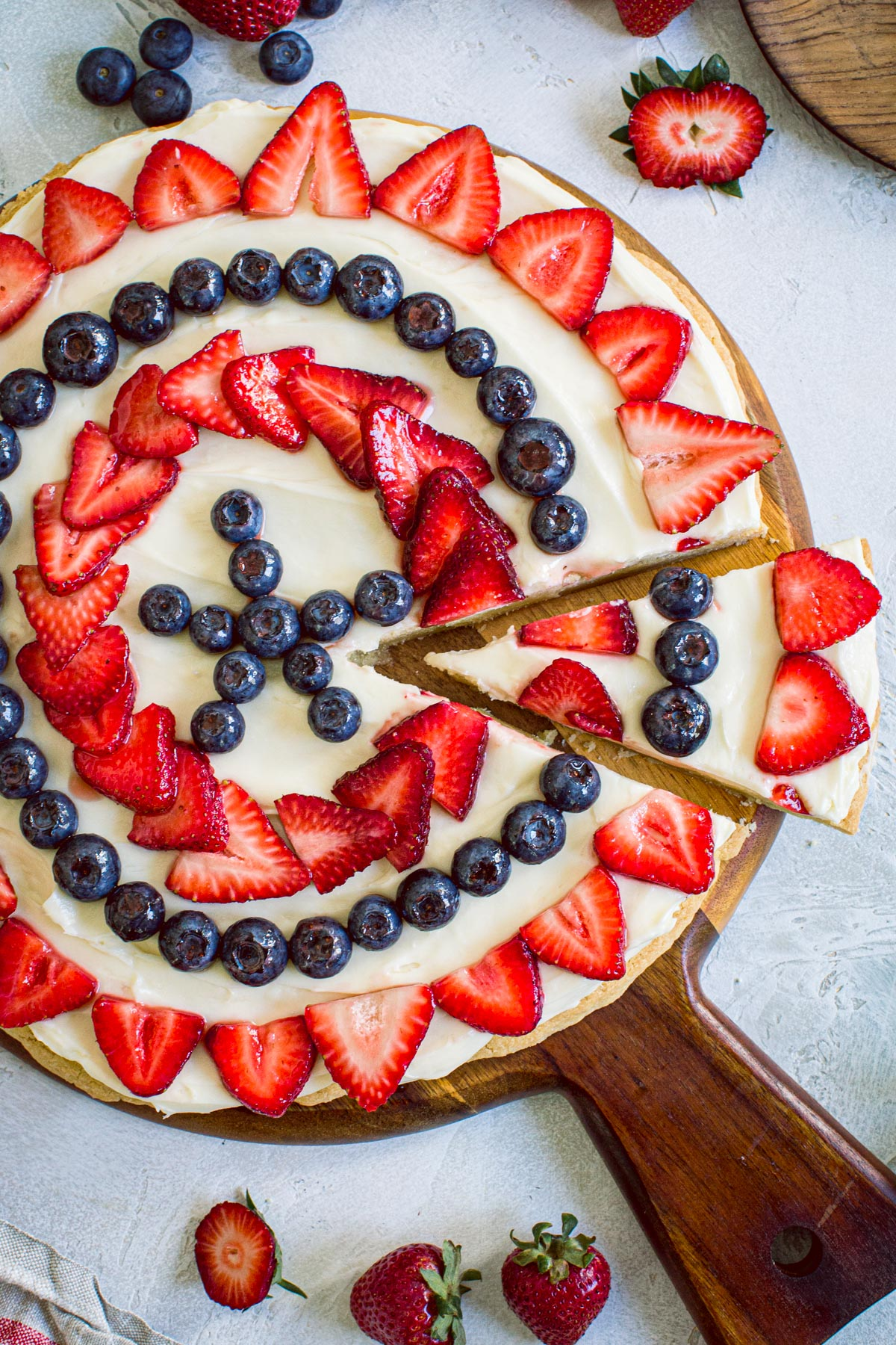 Fourth of July fruit pizza on a round wooden cutting board with strawberries surrounding it.
