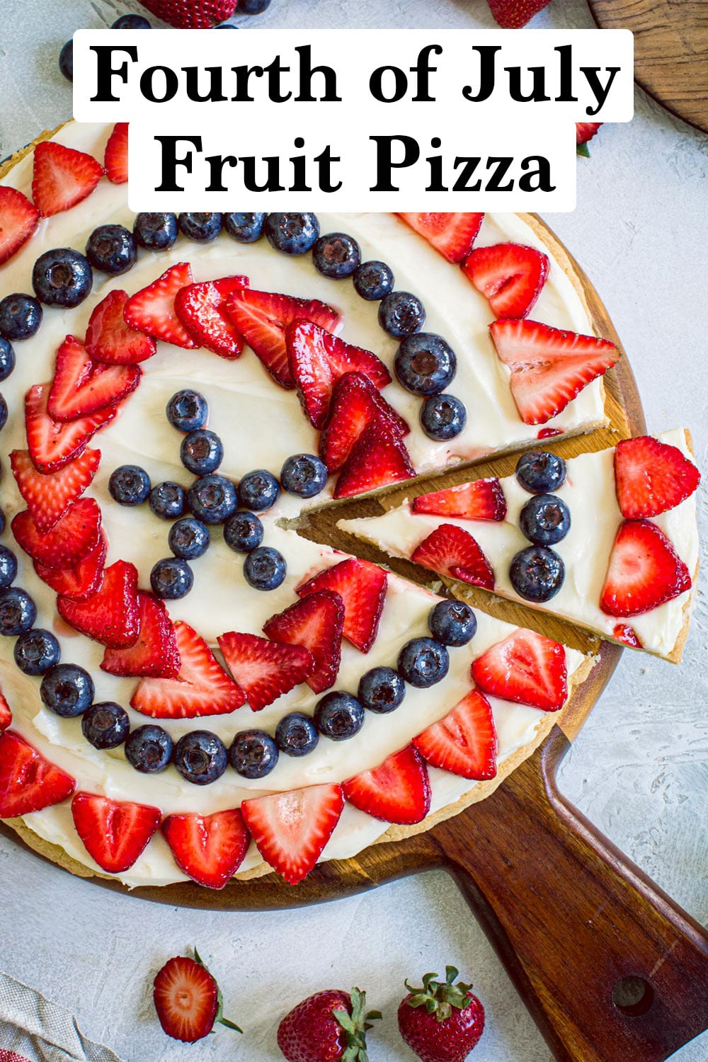 Fruit pizza with a slice cut out on a wooden board.