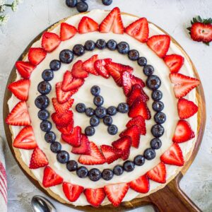 Fourth of July fruit pizza on a round wooden cutting board.