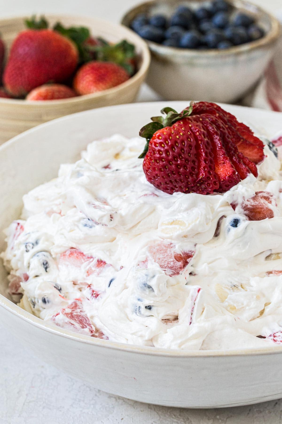 Mixed berry cheesecake salad in a white bowl.