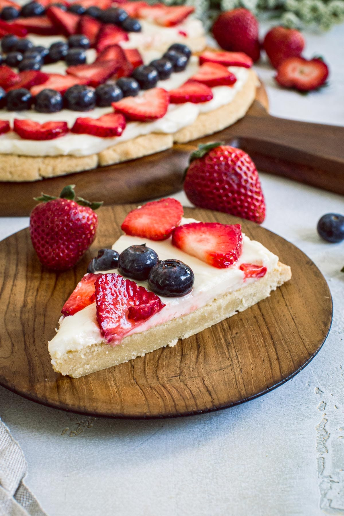 Slice of fruit pizza with strawberries and blueberries on a wooden plate.