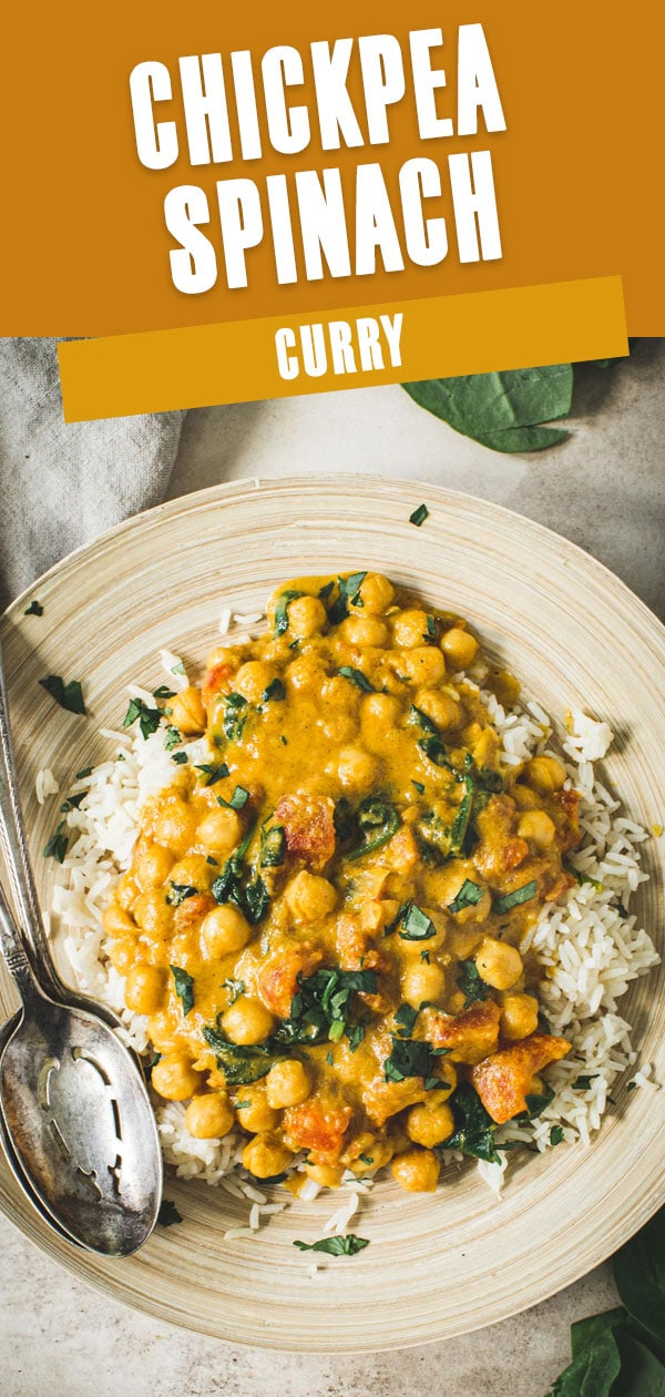 Chickpea spinach curry over rice on a bamboo plate with silver serving spoons.
