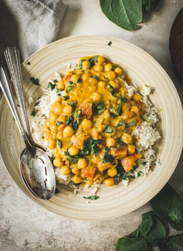 Chickpea spinach curry over rice with silver serving spoons.