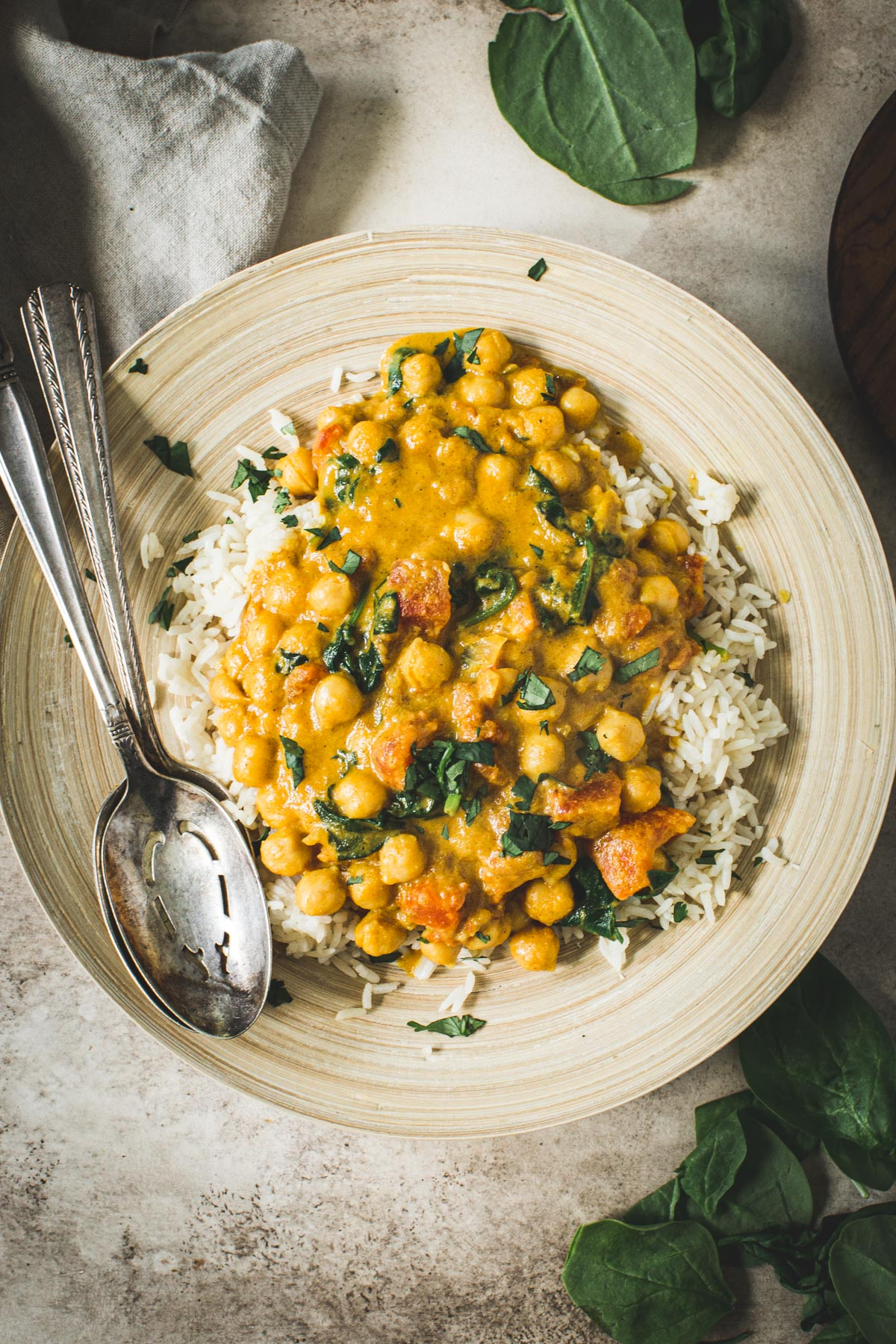 Vegan chickpea spinach curry on a bamboo plate with silver serving spoons.