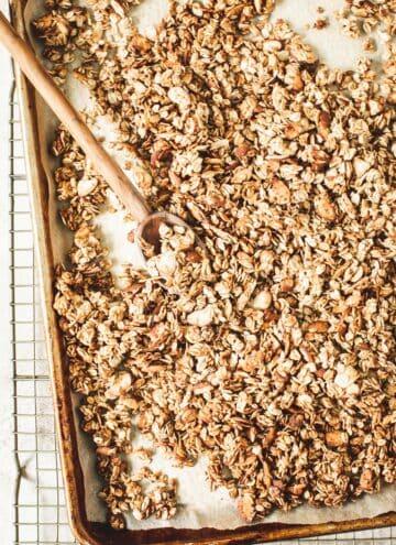 Honey vanilla granola recipe on a rimmed baking sheet.