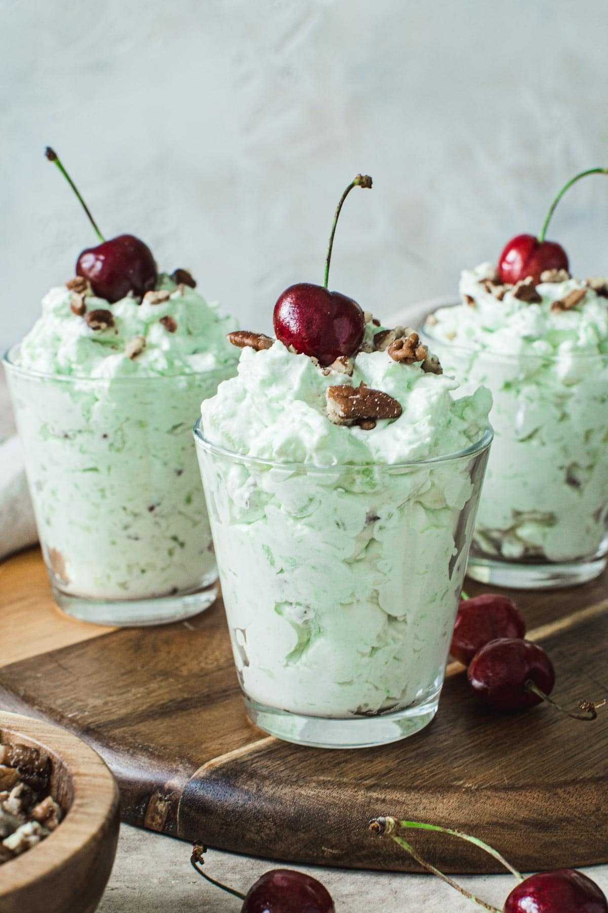 Watergate salad in glasses topped with cherries.