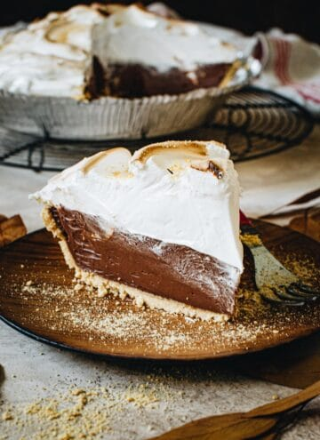 Slice of no-bake s'mores pie on a wooden plate.