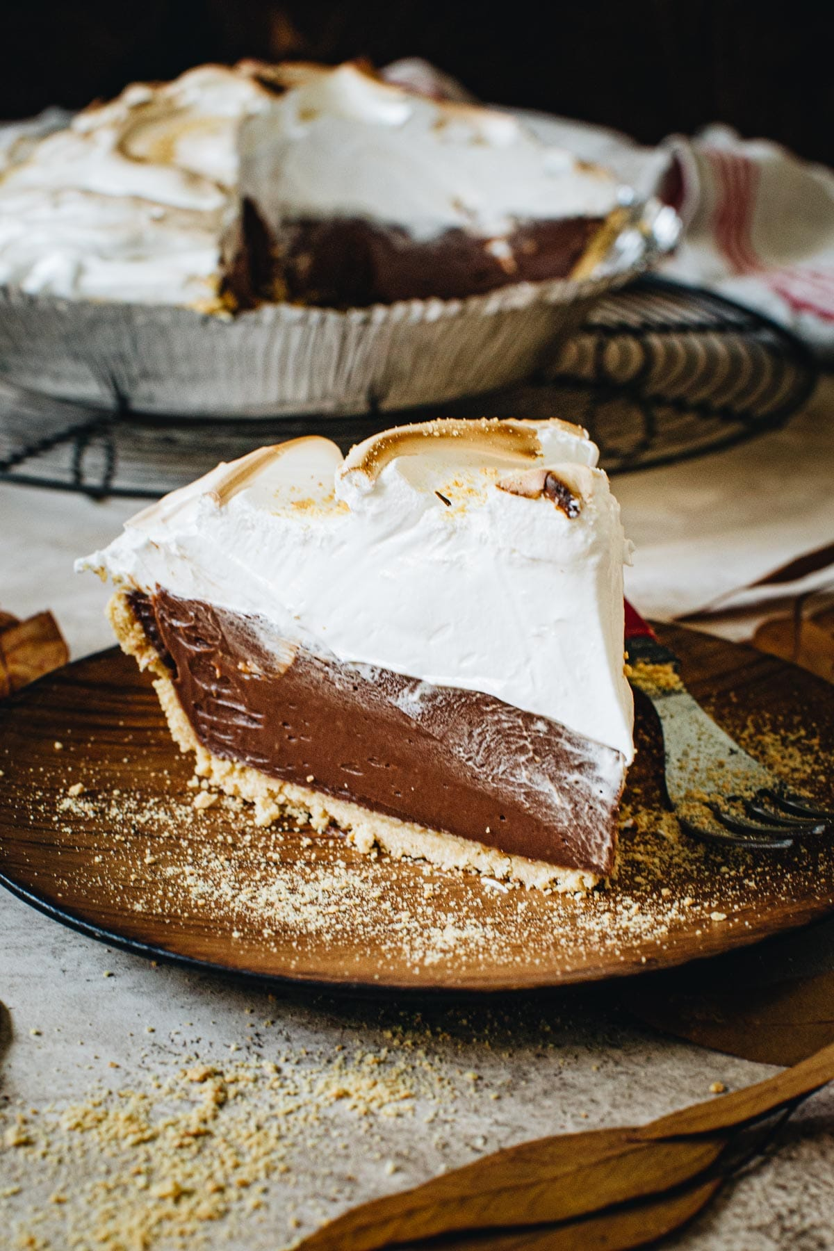 No-bake s'mores pie slice topped with marshmallow meringue on a wooden plate.