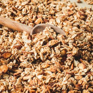 Honey vanilla granola with a wooden spoon scooping it up.
