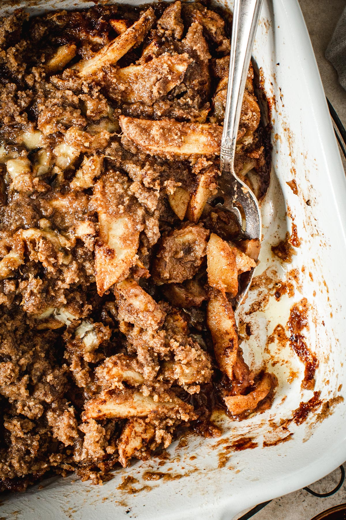 Baked apple crumble without oats in a baking dish with a silver serving spoon.