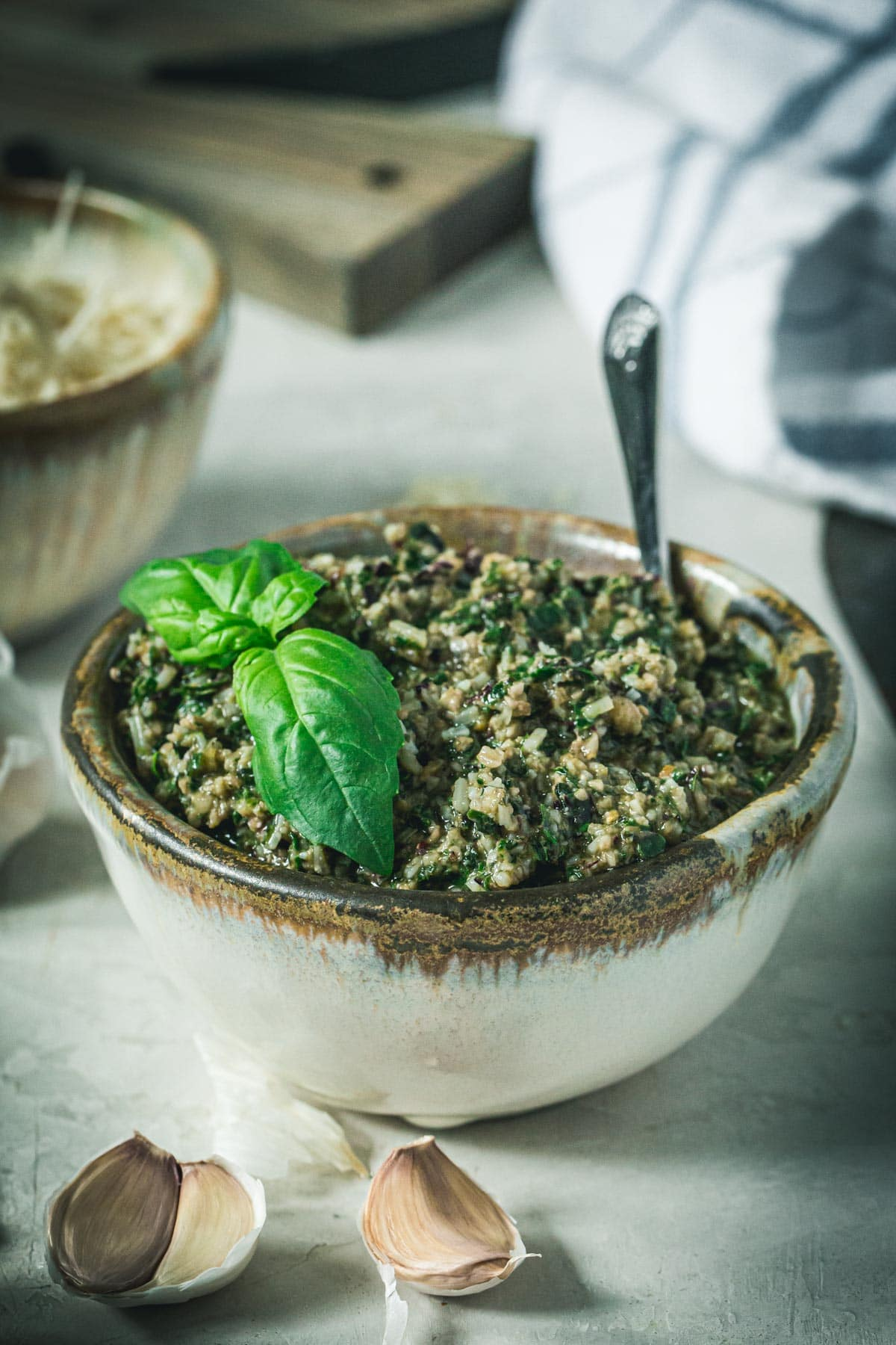 Homemade beet greens pesto topped with basil in a pottery bowl.
