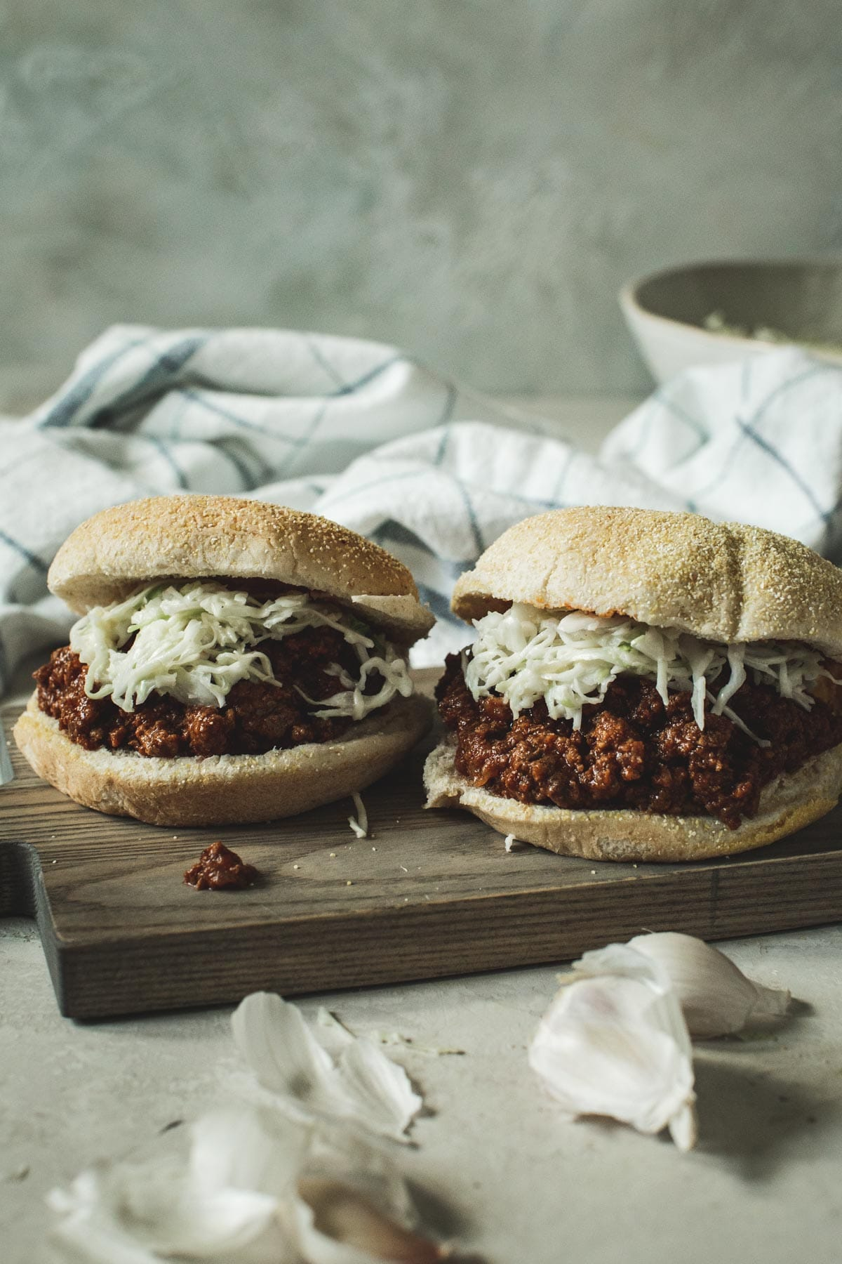 Sloppy Joes topped with coleslaw sitting on a wooden board.