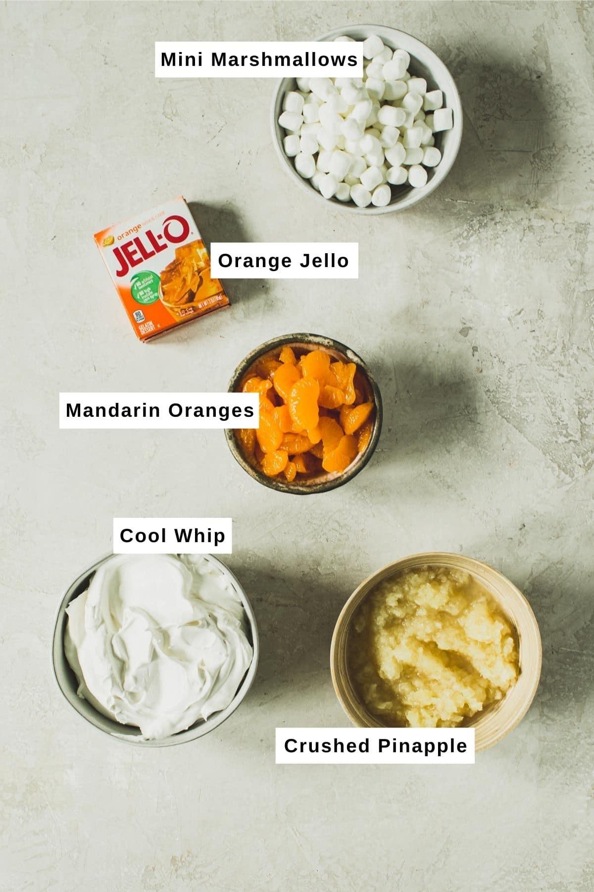 Orange Jello salad ingredients in bowls.
