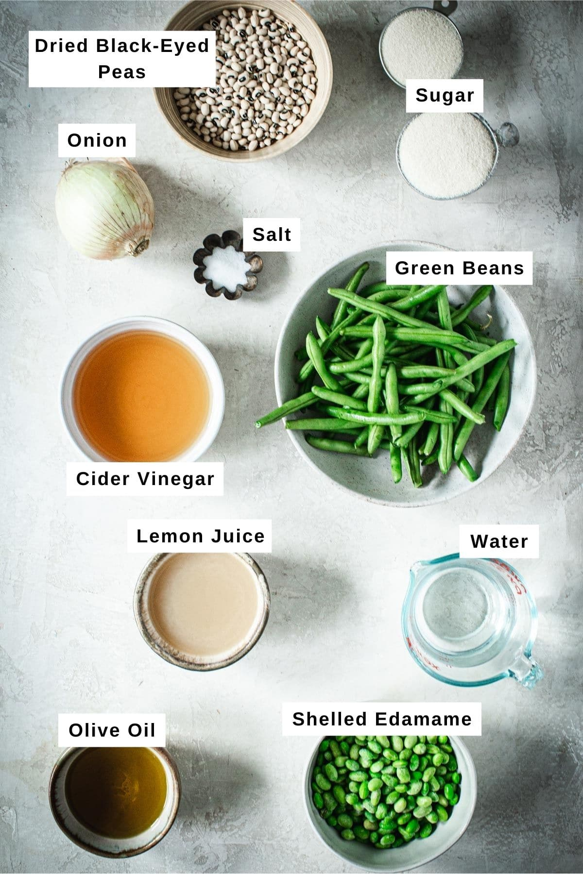 Three bean salad ingredients in different sized bowls.