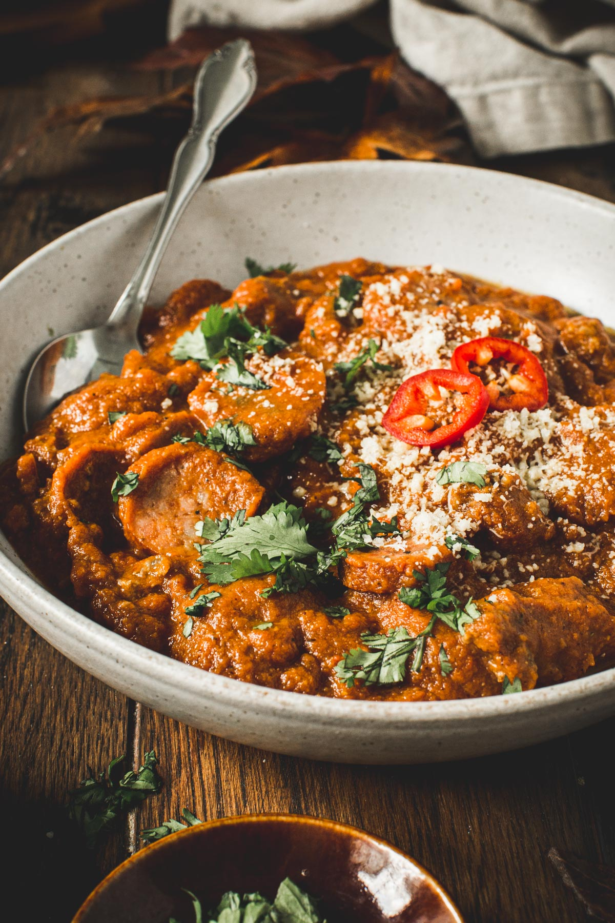 Sausage pumpkin chili topped with cilantro and grated cheese in a bowl.