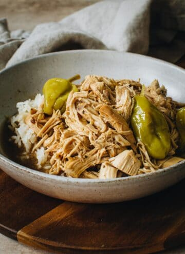 Instant Pot Mississippi chicken over rice and topped with pepperoncini peppers.