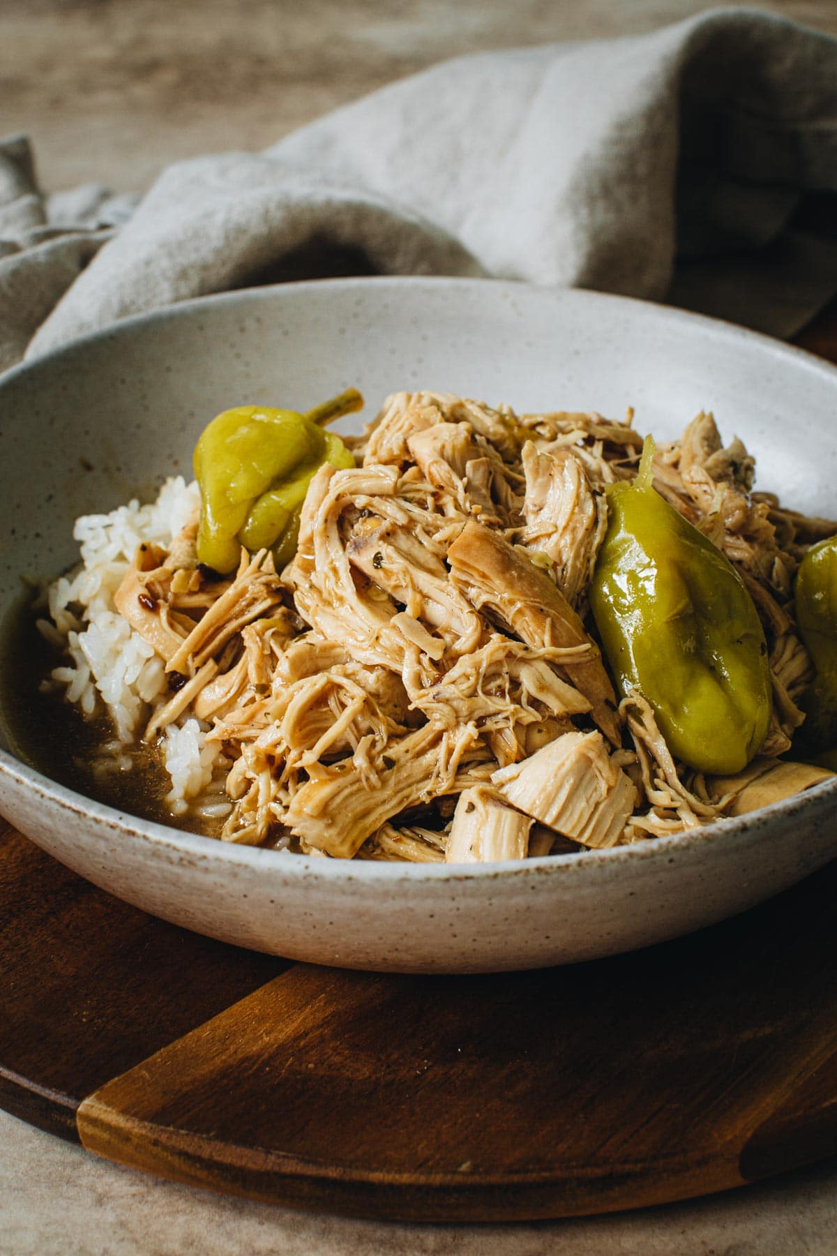 Mississippi chicken topped with pepperoncini peppers in a bowl.