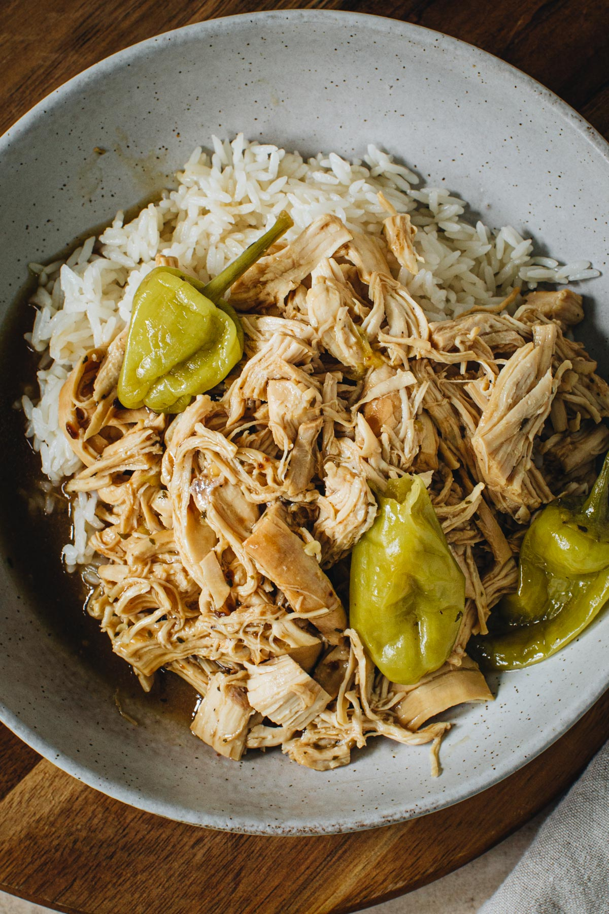 Mississippi chicken over rice in a pottery bowl.