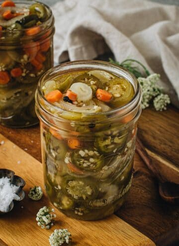 Pickled jalapenos and carrots in a large mason jar.