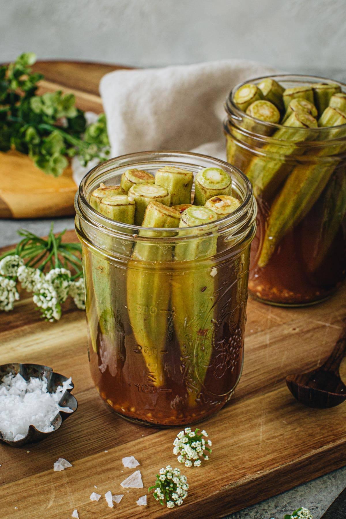 Pickled okra in a vinegar brine in a glass jar.