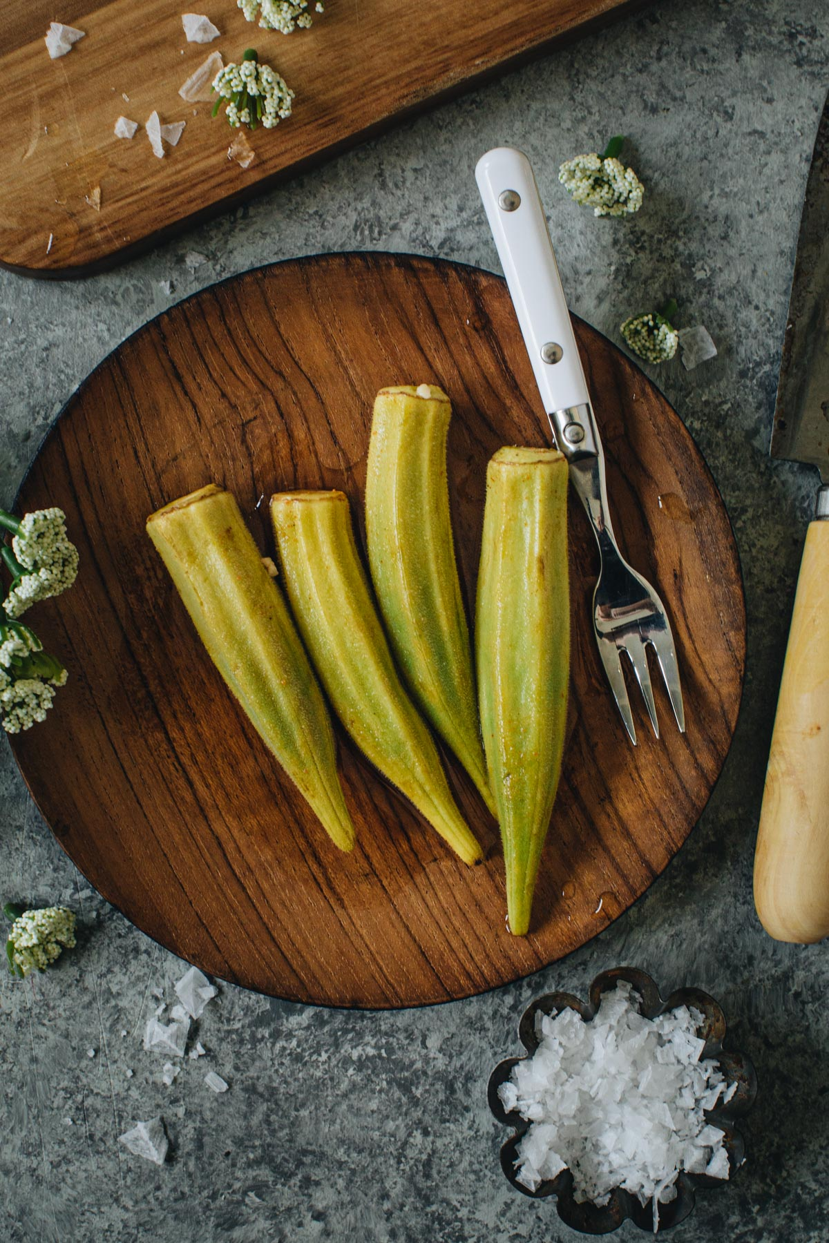 Pickled okra on a wooden plate with a white serving fork.