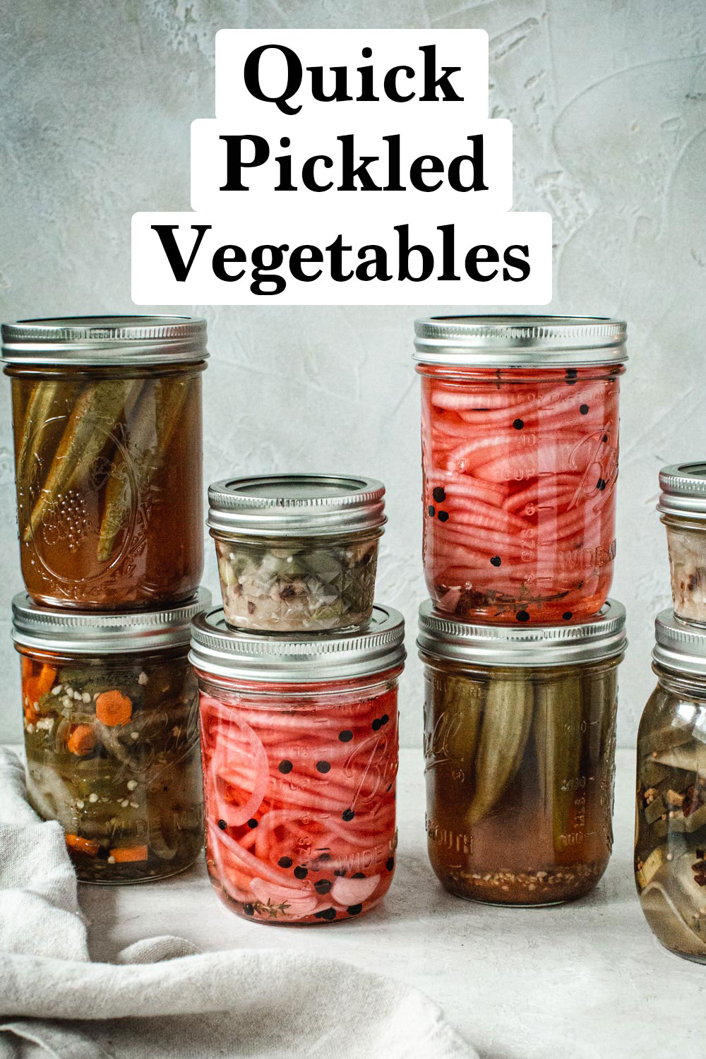 Quick pickled vegetables in jars stacked on each other.