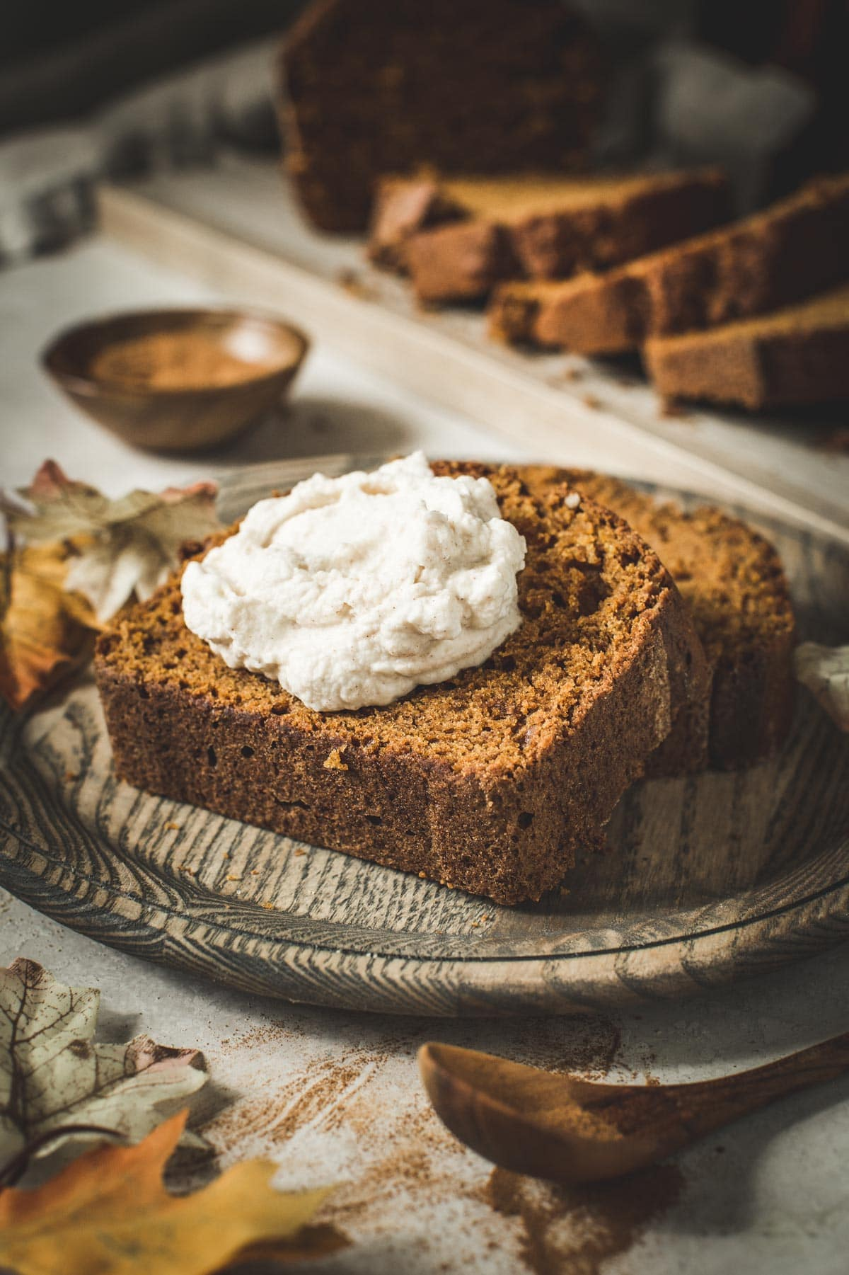 Slice of pumpkin bread topped with whipped cream on a wooden plate.