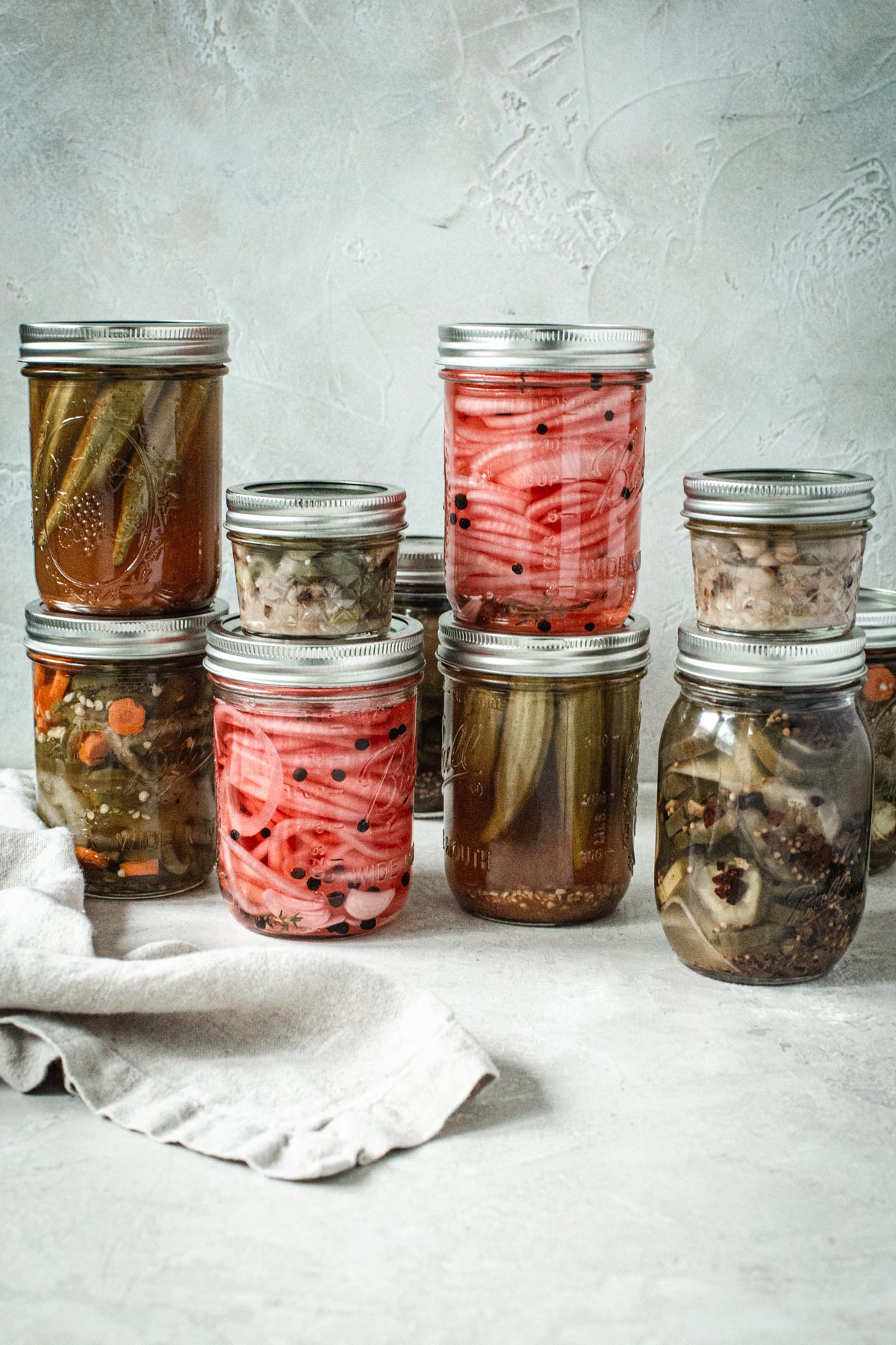 Jars of pickled vegetables stacked on top of each other.